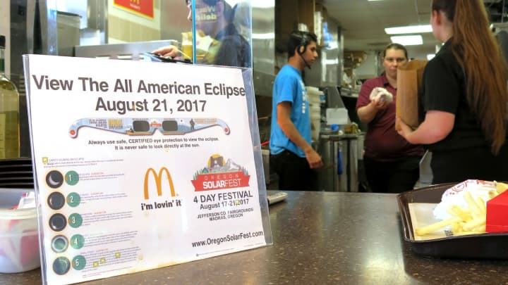 A sign advertising solar eclipse glasses for the Aug. 21, 2017, total solar eclipse hangs in the window of a McDonald's restaurant in Madras, Oregon.