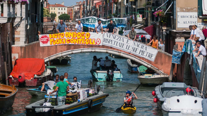 Protesters with banners against mass tourism on a bridge across Misericordia Canal in Venice, Italy on July 2, 2016.