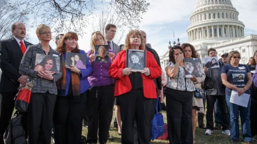 In this April 1, 2014 file photo, families of victims of a General Motors safety defects in small cars hold photos of their loved ones as they gather on the lawn on Capitol Hill in Washington.