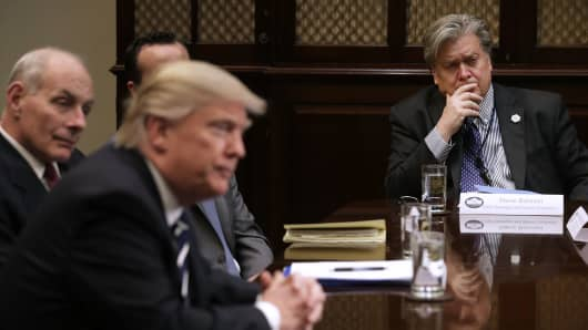 White House Chief Strategist Steve Bannon (R) listens to U.S. President Donald Trump.