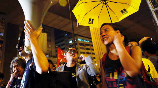 A protester holds a yellow umbrella, the symbol of the Occupy Central movement, in support of jailed Hong Kong student leaders Joshua Wong, Nathan Law and Alex Chow, while officers from the Correctional Services Department stand guard outside a prison in Hong Kong, China August 18, 2017.