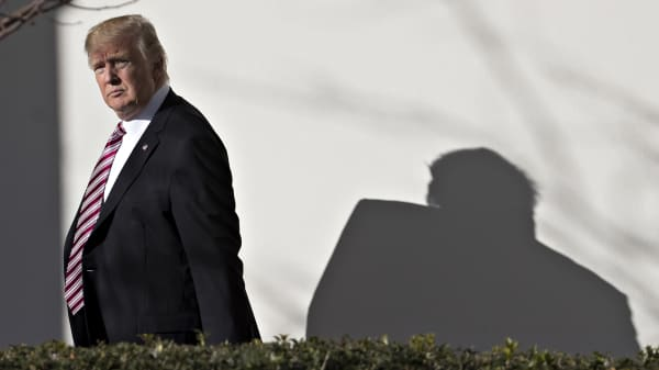 President Donald Trump walks towards the Oval Office through the West Wing Colonnade of the White House.