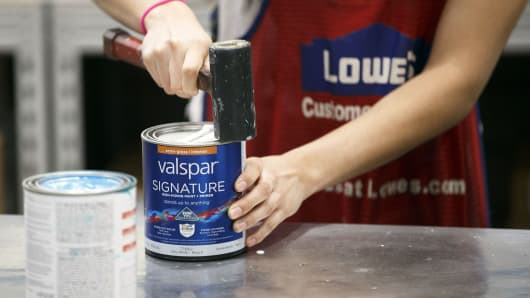 An employee secures the lid of a Valspar Corp. paint can for a customer inside a Lowe's store in Burbank, California.