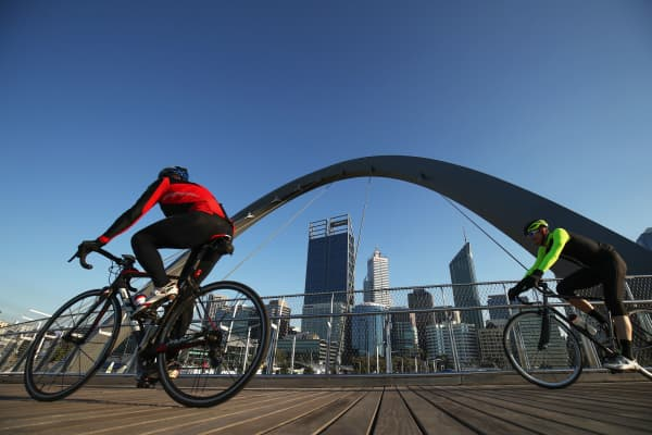 Cyclists cross the Elizabeth Quay Bridge in the central business district of Perth, Australia.