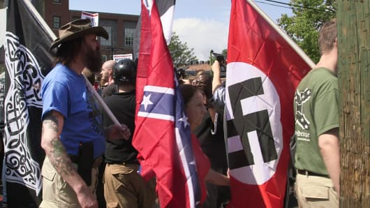 Demonstrators carry confederate and Nazi flags during the Unite the Right free speech rally at Emancipation Park in Charlottesville, Virginia, on August 12, 2017.