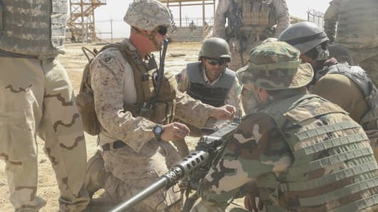 A U.S. Marine advisor demonstrates proper firing techniques on a machine gun to Afghan National Army soldiers during a live-fire range at Camp Shorabak, Afghanistan, Aug. 17, 2017.