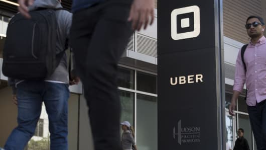 Pedestrians walk past the Uber Technologies headquarters building in San Francisco, June 21, 2017.