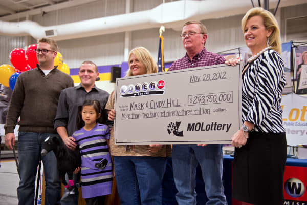 Cindy and Mark Hill, center and second from right, stand with a ceremonial check from the Missouri Lottery for $293,750,000 during the news conference, Friday, November 30, 2012.
