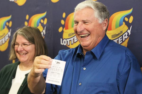 Merle Butler, right, standing next to his wife Patricia Butler, holds up the winning Lottery ticket, Wednesday, April 18, 2012.