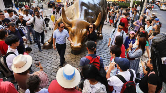 People gather for pictures around the Charging Bull in New York City.