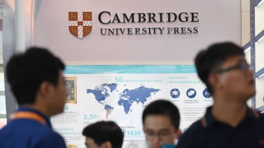 People stand outside the Cambridge University Press stand at the Beijing International Book Fair in Beijing on August 23, 2017.