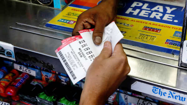 A customer purchases Powerball lottery tickets for a $700 million jackpot at a newsstand in New York City, August 23, 2017.