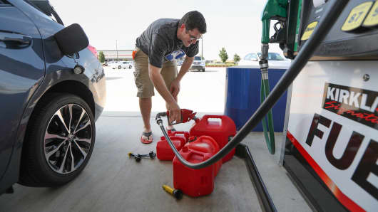 A customer fills his vehicle and five gas cans at Costco in preparation for tropical weather on Wednesday, Aug. 23, 2017, in Pearland, Texas.