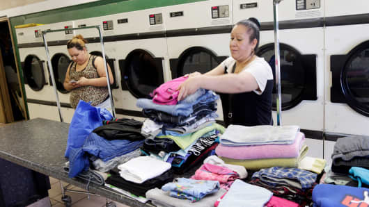 A woman folds her family's laundry in East Palo Alto, Calif.