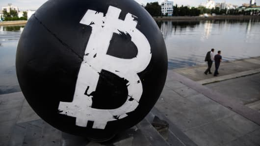 The Bitcoin cryptocurrency symbol on a stone sphere monument painted black by unidentified persons in Oktyabrskaya Square in Yekaterinberg, Russia.