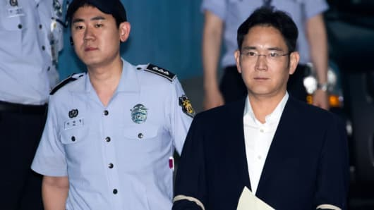 Jay Y. Lee, co-vice chairman of Samsung Electronics, right, is escorted by a prison officer as he arrives at the Seoul Central District Court in Seoul, South Korea, on Monday, July 10, 2017.