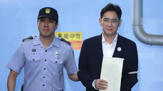 Jay Y. Lee, co-vice chairman of Samsung Electronics Co., right, is escorted by a prison officer as he leaves the Seoul Central District Court in Seoul, South Korea, on Friday, Aug. 25, 2017.