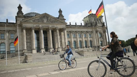 Visitors ride bicycles past the Reichstag, seat of the German parliament, the Bundestag, on July 13, 2015 in Berlin, Germany.