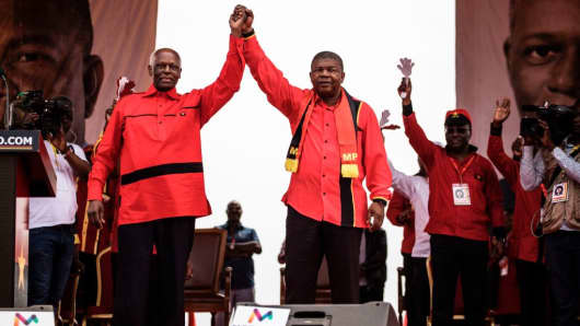 Outgoing Angolan President Jose Eduardo dos Santos and MPLA presidential candidate Joao Lourenco hold hands during the closing campaign rally in Luanda, Angola, on August 19, 2017.