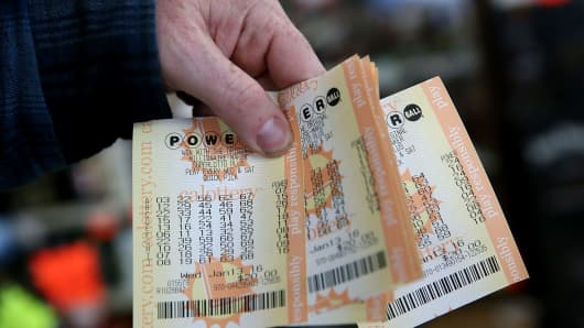 A customer holds a handful of Powerball tickets.