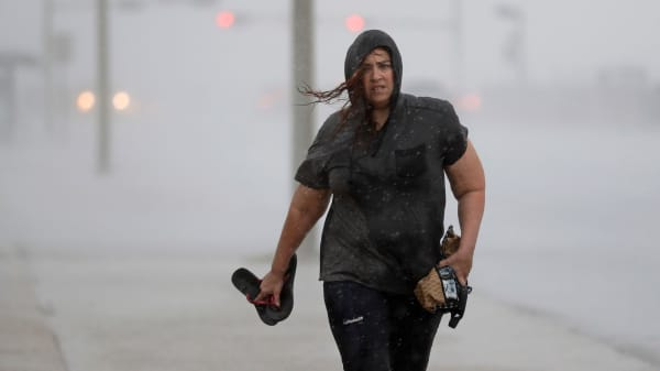A woman walks along the seawall in Galveston, Texas as Hurricane Harvey intensifies in the Gulf of Mexico Friday, Aug. 25, 2017.
