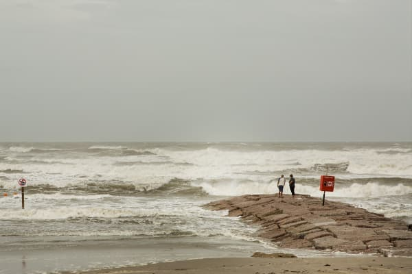 People stand on seawall by the Gulf of Mexico ahead of Hurricane Harvey in Galveston, Texas, U.S., on Friday, Aug. 25, 2017. Hurricane Harvey strengthened as it headed toward landfall in Texas, forecast to become the worst storm to strike the region in more than a decade.
