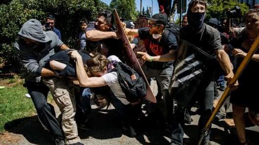 Demonstrators clash as as they beat up a man during counter protest against white supremacist at MLK Park in Berkeley, Calif., on Aug. 27, 2017.