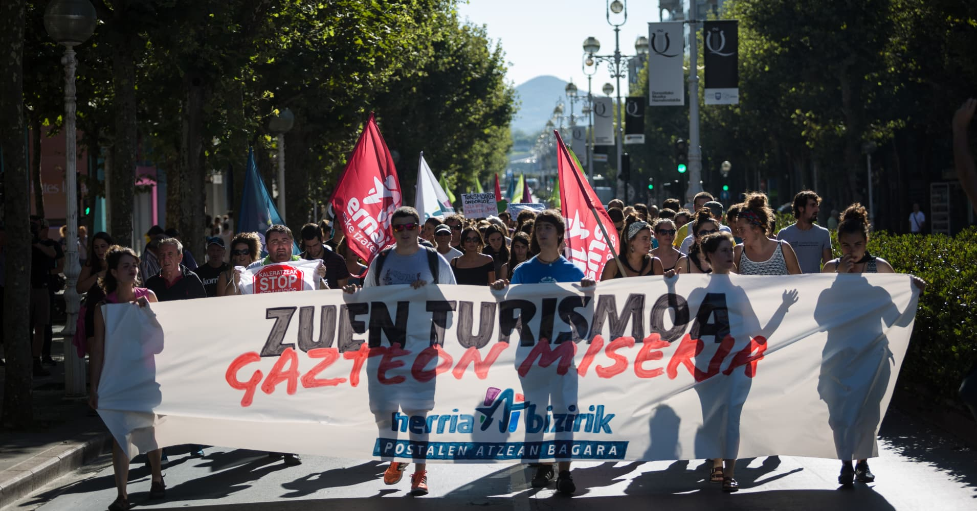 Protesters march holding a banner reading 'Your tourism is misery for the young' in San Sebastian, Spain on August 17, 2017.
