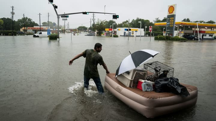 A resident floats his pets and belongings on an air mattress along Mercury Drive as he flees flood water at his home in Houston, TX on Sunday, Aug 27, 2017.