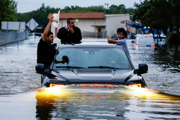 Residents use a truck to navigate through flood waters from Tropical Storm Harvey in Houston, Texas, August 27, 2017.