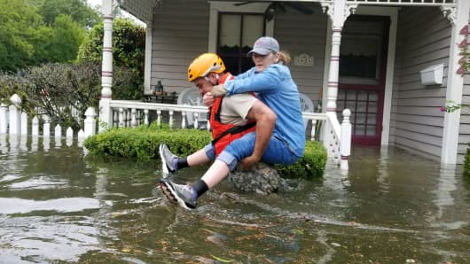 A Texas National Guard soldier carries a woman on his back as they conduct rescue operations in flooded areas around Houston.