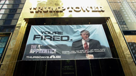 A banner promoting the television show 'The Apprentice' hangs from the entrance of Trump Tower on March 19, 2004.