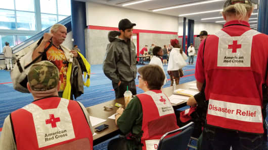 Evacuees arrive to seek shelter with Red Cross volunteers at the George Brown convention center after flood waters of Hurricane Harvey forced them to leave their homes in Houston, Texas, August 27, 2017.