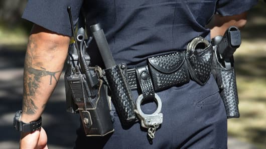 A policeman equipped with a Glock revolver, handcuffs and a radio on his belt patrols a street in Santa Fe, New Mexico.