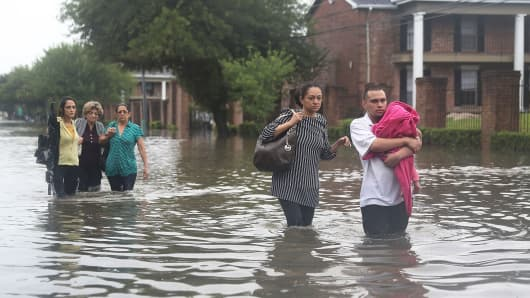 People walk down a flooded street as they evacuate their homes after it the area was inundated with flooding from Hurricane Harvey on August 27, 2017 in Houston, Texas.