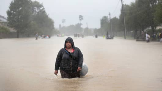 People make their way out of a flooded neighborhood after it was inundated with rain water, remnants of Hurricane Harvey, on August 28, 2017 in Houston, Texas