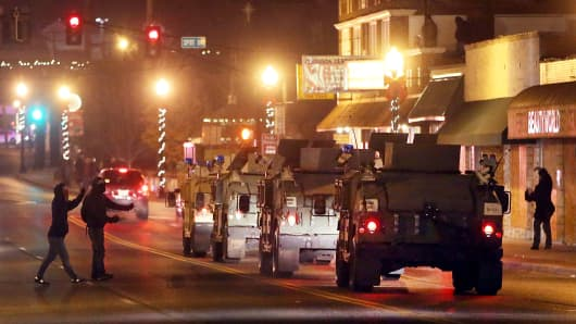 Protestors confront a convoy of Missouri National Guard humvees as they drive near the Ferguson police station on November 25, 2014 in Ferguson, Missouri.