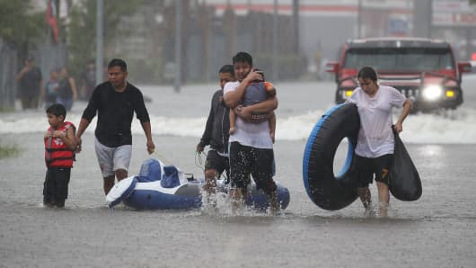 People walk down a flooded street as they evacuate their homes after the area was flooded from Hurricane Harvey on August 27, 2017 in Houston, Texas.