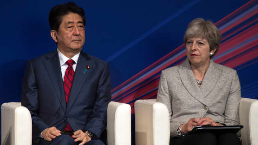 Britain's Prime Minister, Theresa May, sits with Japan's Prime Minister, Shinzo Abe as they attend a Japan-UK Business Forum on August 31, 2017 in Tokyo, Japan.