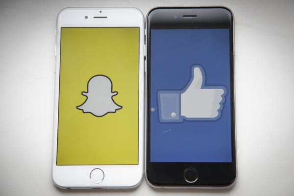 Snapchat and Facebook logos pictured on smartphones