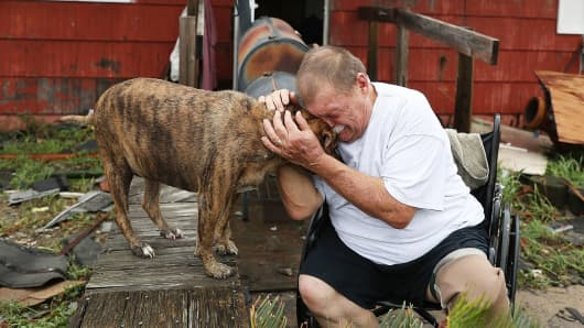 Steve Culver cries with his dog Otis as he talks about what he said was the, 'most terrifying event in his life,' when Hurricane Harvey blew in and destroyed most of his home while he and his wife took shelter there on August 26, 2017 in Rockport, Texas.