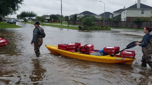 Pizza Hut employees deliver free pizzas by kayak to families trapped in their homes by Hurricane Harvey