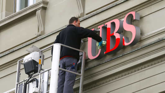 A man cleans the logo of Swiss bank UBS on a branch in Bern.