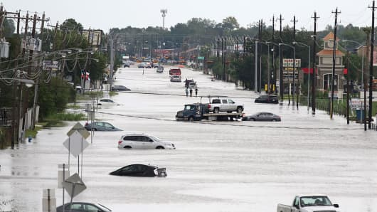 A car gets towed while men walk in the flooded waters of Telephone Rd. in Houston, Texas on August 30, 2017.