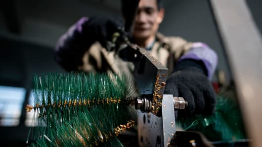 A worker cutting fake 'branches' into pieces at a artificial Christmas tree factory in Yiwu city, located in the Zhejiang province of China.