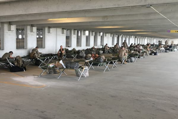 Members of the army in town for Hurricane Harvey rescue pitch cots in the Academy Sports + Outdoors parking garage.