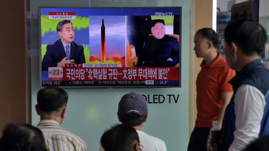 People watch a television display at a train station in Seoul on September 3, 2017 showing a news broadcast about North Korea's latest possible nuclear test.