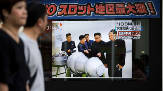 Pedestrians walk past a monitor showing an image of North Korean leader Kim Jong Un in a news program reporting on North Korea's 6th nuclear test on September 3, 2017 in Tokyo, Japan.
