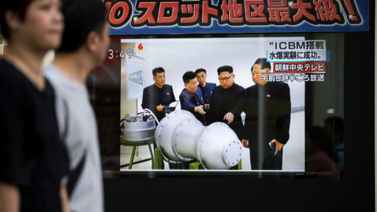 Pedestrians walk past a monitor showing an image of North Korean leader Kim Jong-Un in a news program reporting on North Korea's 6th nuclear test on September 3, 2017 in Tokyo, Japan.