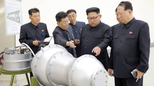This undated picture released by North Korea's official Korean Central News Agency (KCNA) on September 3, 2017 shows North Korean leader Kim Jong-Un (C) looking at a metal casing with two bulges at an undisclosed location.